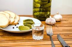 Vodka, inlagda gurkor, bröd och vitlök på en trätabell royaltyfria bilder