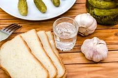 Vodka, inlagda gurkor, bröd och vitlök på en trätabell royaltyfri fotografi