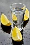 Vodka with lemon. Vodka shot with lemon on glack wet glass Stock Photo