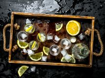 Vodka with lemon and ice on a wooden tray. On the black chalkboard Stock Photos