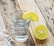 Vodka with lemon on wooden background Stock Photo