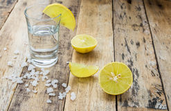 Vodka with lemon on wooden background Stock Photography