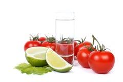 Vodka, limefrukt och grupp av tomater över vit Royaltyfri Bild