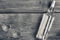 Black and white photo. VODKA luxury. Vodka in a bottle and glasses on a background of wood. stock photos