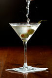 Vodka martini. Dirty vodka martini splashing into a cocktail glass with green olives Royalty Free Stock Photography