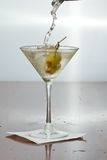 Vodka martini. Dirty vodka martini splashing into a cocktail glass with green olives Royalty Free Stock Images
