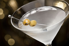 Vodka Martini with olive garnish. In front of a gold glitter background Stock Photo