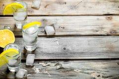 Vodka med is i sköt exponeringsglas och skivor av citronen royaltyfria bilder