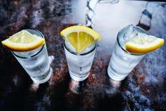 Vodka ou genièvre ou tequila dans des verres à liqueur sur la table en pierre images stock