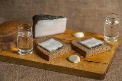 Vodka, pan, tocino en un fondo marrón Fotos de archivo