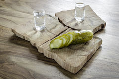 Vodka and pickled cucumber. Pickled cucumber and vodka on old wooden table Royalty Free Stock Image