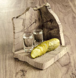 Vodka and pickled cucumber. Pickled cucumber and vodka on old wooden table Stock Photos