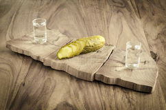 Vodka and pickled cucumber. Pickled cucumber and vodka on old wooden table Royalty Free Stock Photography