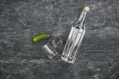 Vodka with pickled cucumbers and two shot glasses on a black wooden background. Stock Image