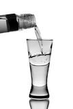 Vodka pour into glass. (isolated on white Stock Image