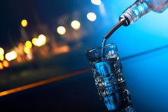 Vodka is poured from the bottle into a glass royalty free stock photography