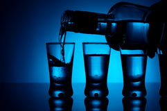 Vodka poured into a glass with glasses lit with blue backlight Royalty Free Stock Photos
