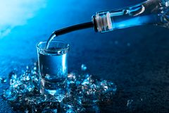 Vodka poured into a glass lit with blue backlight royalty free stock photography