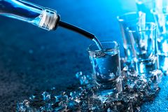 Vodka poured into a glass lit with blue backlight royalty free stock images