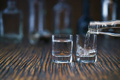 Vodka pouring from the bottle into two shot glass in a bar, sele. Russian vodka pouring from the bottle into two shot  glass in a bar, selective  focus Royalty Free Stock Image