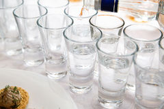 Vodka pours from a bottle in a shot standing on the white table. Photo of vodka pours from a bottle in a shot standing on the white table Royalty Free Stock Photo