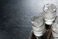 Vodka on the rocks on an old wooden table as detailed close-up shot. Closeup Stock Photo