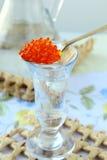 Vodka russe avec une cuillerée de caviar rouge Images stock