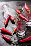 Vodka shot with chili peppers on rusty grunge table Stock Photo