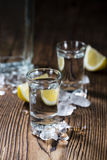 Vodka. Shot of ice cold Vodka on rustic wooden background Stock Images