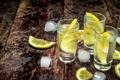 Vodka shots with ice and lemon. On a wooden background Stock Images