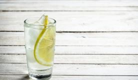 Vodka shots with lemon and ice. On a white wooden table Royalty Free Stock Image