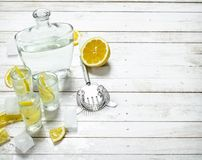 Vodka shots with lemon and ice. On a white wooden table Stock Images