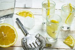 Vodka shots with lemon and ice. On a white wooden table Royalty Free Stock Photos