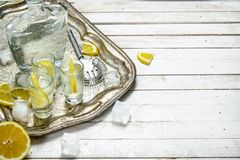 Vodka shots with lemon and ice. On a white wooden table Royalty Free Stock Photography