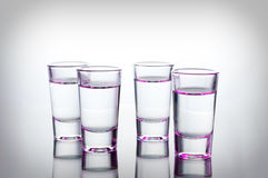 Vodka shots lighted with pink light filled with alcohol on glass bar table Royalty Free Stock Images