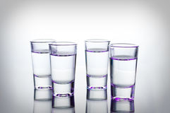 Vodka shots lighted with purple light filled with alcohol on glass bar table Stock Photo