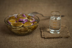 Vodka and a snack of pickled mushrooms on brown background Stock Image