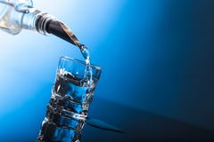 Vodka som häller från flaskan in i exponeringsglas i en stång royaltyfria foton
