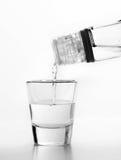 Vodka som hälls till ett exponeringsglas Vit bakgrund fotografering för bildbyråer