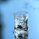 Vodka splash on blue Royalty Free Stock Images