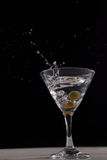 Vodka splashing in martini glass with olives. Against black background Royalty Free Stock Photography
