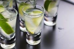 Vodka, tequila, gin, alkoholcoctail med is och limefrukt på en svart bakgrund En restaurang stång Ett parti royaltyfri bild