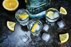 vodka Tiros, vidros com vodca e limão com gelo Fundo de pedra escuro fotos de stock