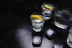 vodka Tiros, vidros com vodca e limão com gelo Fundo de pedra escuro imagem de stock