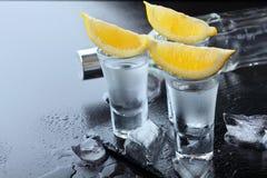 vodka Tiros, vidros com vodca e limão com gelo Fundo de pedra escuro Copie o espaço Foco seletivo foto de stock