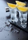 vodka Tiros, vidros com vodca e limão com gelo Fundo de pedra escuro Copie o espaço Foco seletivo imagem de stock