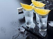vodka Tiros, vidros com vodca e limão com gelo Fundo de pedra escuro Copie o espaço Foco seletivo imagens de stock