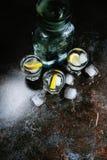 vodka Tiros, vidros com vodca e limão com gelo Fundo de pedra escuro Imagem vertical imagens de stock