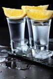 vodka Tiros, vidros com vodca com limão Fundo de pedra escuro Copie o espaço closeup Foco seletivo imagens de stock