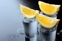 vodka Tiros, vidros com vodca com limão Fundo de pedra escuro Copie o espaço closeup Foco seletivo imagem de stock royalty free